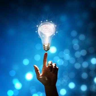 창의적이고 혁신적 영감을 주는 두뇌와 전구에 사업가 손끝