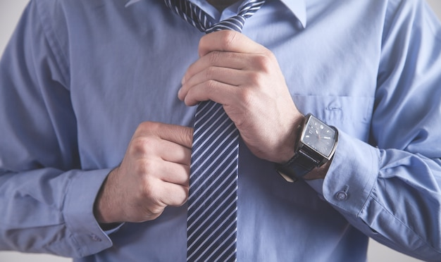 Бизнесмен, поправляющий галстук. бизнес-концепция