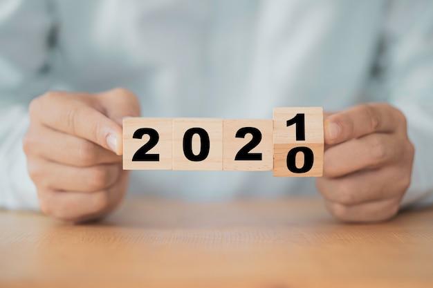 시작 새해 사업 계획을 위해 2020 년에서 2021 년을 뒤집는 사업가.