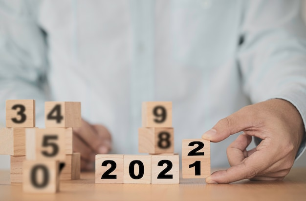 Businessman flipping 2021 to 2022 year for start new year business plan.