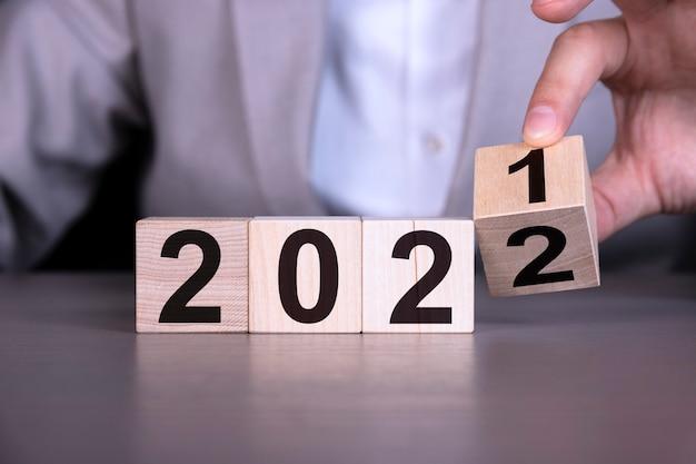 ビジネスマンは2021年から2022年に変更するために木製の立方体を裏返します