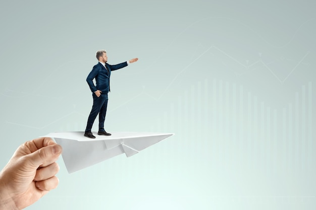 Businessman flying on a paper airplane with the pushing hand of an investor