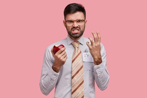 Uomo d'affari in abiti formali tenendo la mela