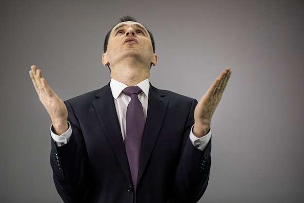 Businessman in formal clothes raising hands, prays for stop financial crisis