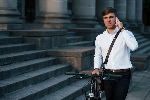 Businessman in formal clothes with black bicycle is in the city.