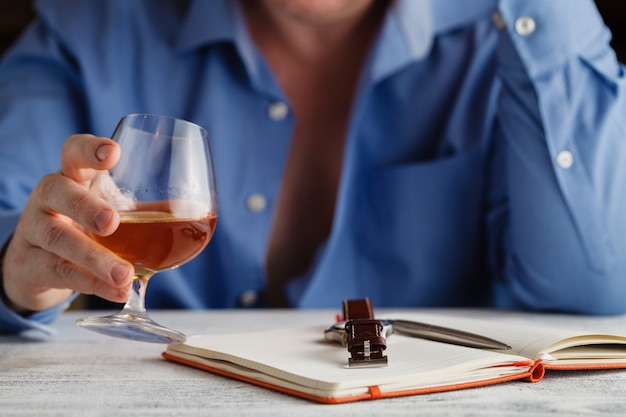Businessman in formal dress relax with glass of cognac