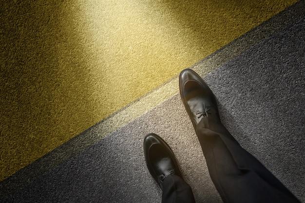 Businessman on formal dress steps into start line