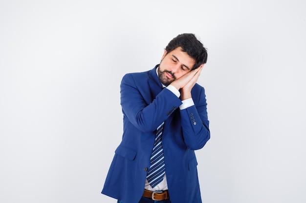 Uomo d'affari in abito formale che si appoggia la guancia sulle mani e sembra assonnato, vista frontale.