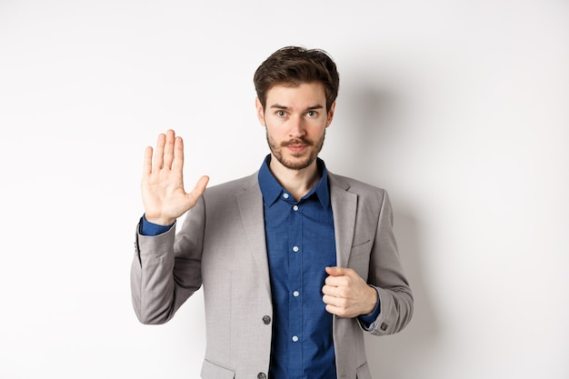 Businessman in formal suit raising hand up to say hello, contactless greeting, smiling friendly, standing on white background.