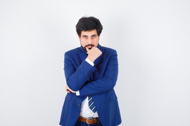 Uomo d'affari in abito formale in piedi in posa di pensiero e guardando serio, vista frontale.