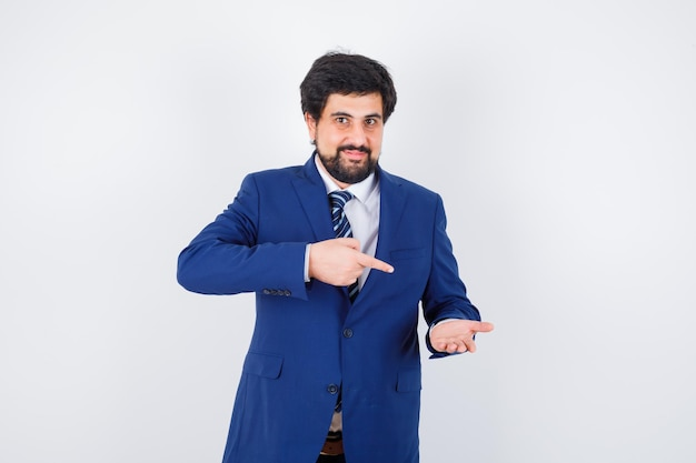 Uomo d'affari in abito formale allungando una mano come tenendo qualcosa, indicandolo e guardando felice, vista frontale.