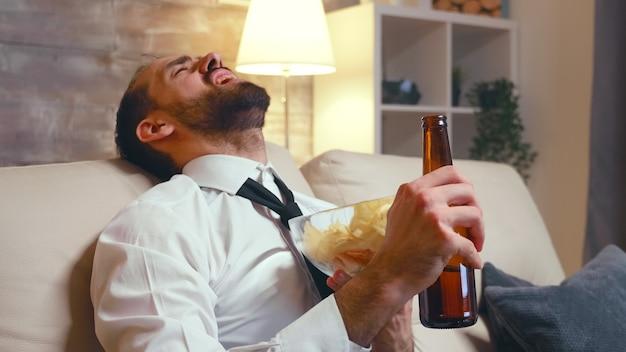Uomo d'affari in abbigliamento formale che mangia patatine da una ciotola. imprenditore che ride guardando la tv.