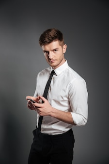 Businessman in formalwear holding mobile phone