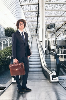 Businessman in front of an escalator in a modern office