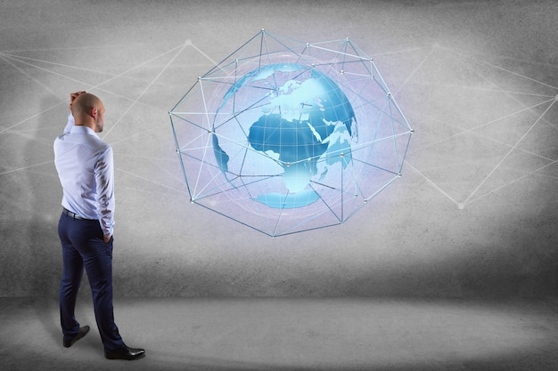 Businessman in front of a wall with a connected network over a earth globe concept