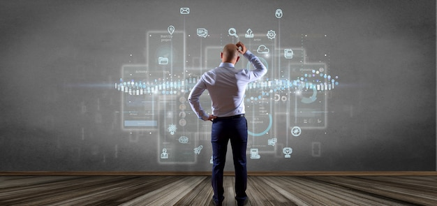 Businessman in front of a wall with user interface screens with icon, stats and data