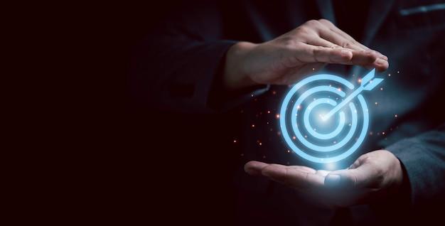 Businessman gesture protecting virtual blue dartboard with arrow ,business achievement objective target concept.
