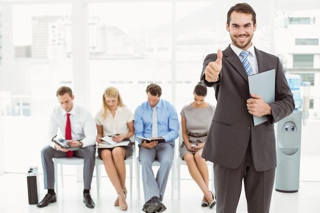 インタビューを待っている人々に対して、ビジネスマンの身振りの親指