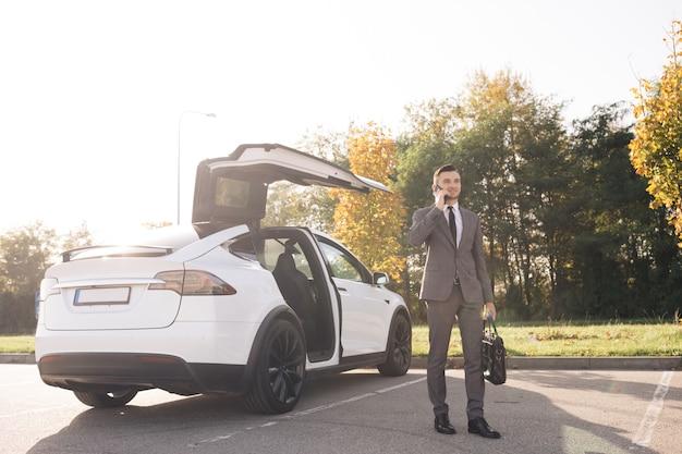Бизнесмен выходит из белого автомобиля представительского класса на автостоянке в дневное время w