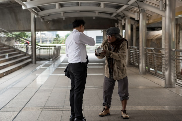 Businessman give money to old homeless