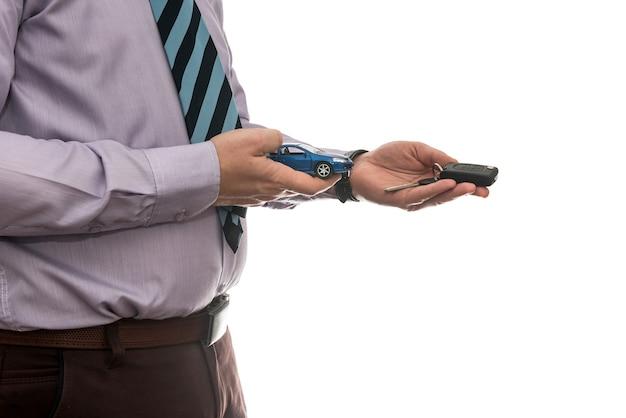 Businessman gives car keys to car isolated