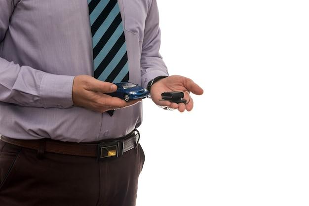 Бизнесмен дает ключи от машины, изолированные на белой стене