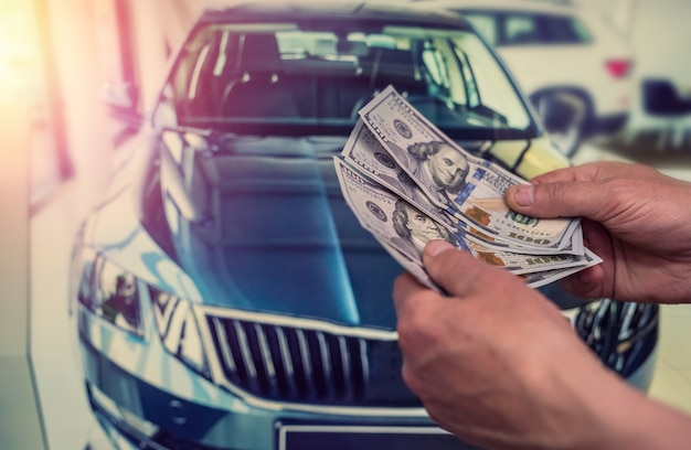 Businessman gives money to rent a car for summer vacation. finance concept