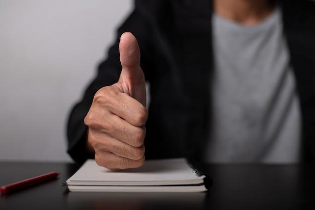 Бизнесмен дает большие пальцы руки вверх