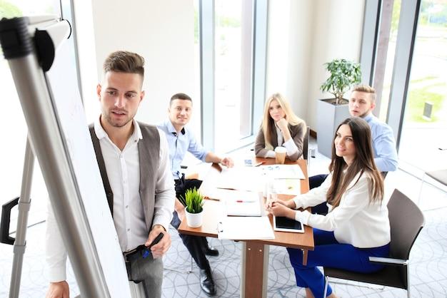 フリップチャートでプレゼンテーションを行うビジネスマン。チームワークの概念
