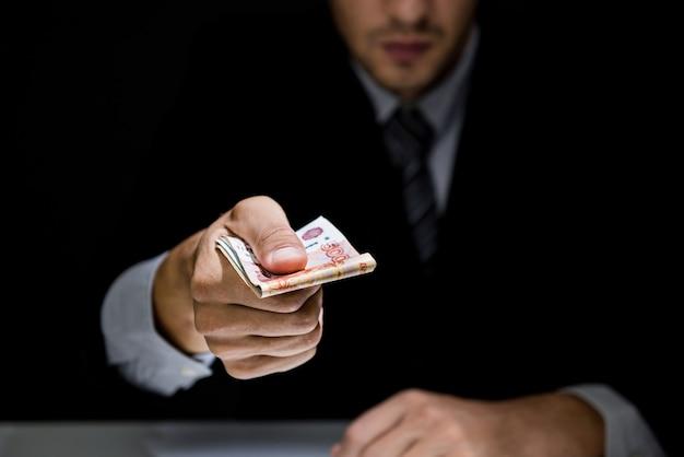 Businessman giving bribe money in dark shadow