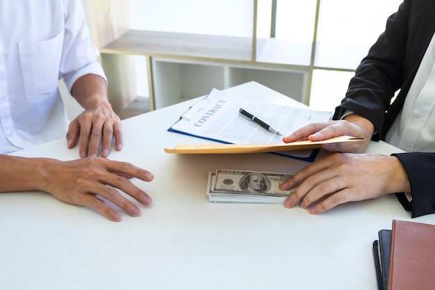 Businessman giving bribe money in the envelope of their partner to give success the deal contract
