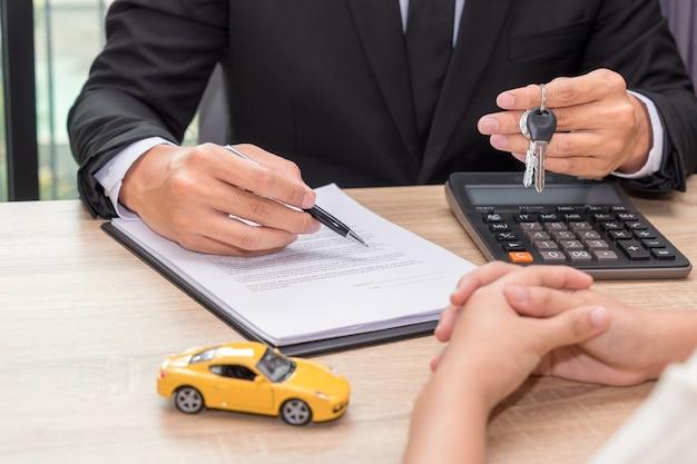 車のキーを与えて、木製の机の上に車のモデルとローン契約について説明するビジネスマン。