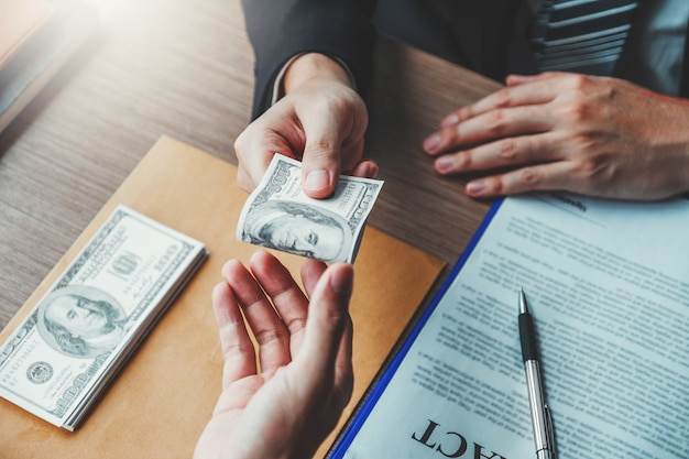 Businessman giving dollar bills to business manager to deal contract