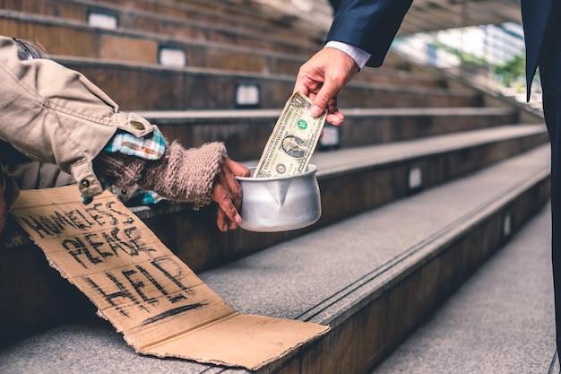 眠っている古いホームレスの人と寄付ドルの現金を与えるビジネスマン