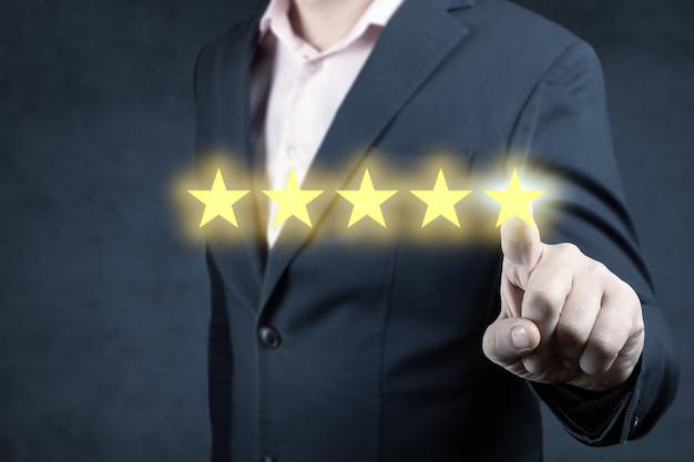 5つ星の評価を与えるビジネスマン、評価会社を増やすために5つ星の視覚的なシンボルを指しています
