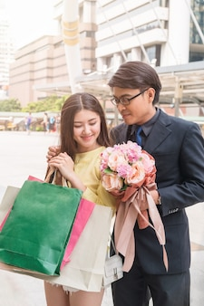Businessman giving flower bouquet with beauty asian woman with paper bag from shopping