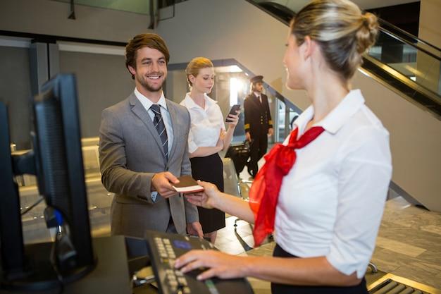 Бизнесмен дает свой посадочный талон женскому персоналу на стойке регистрации