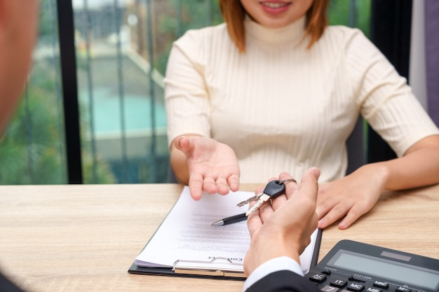 Businessman giving a house key or car key in font of loan contract.