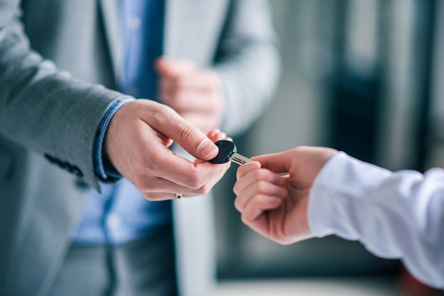 Businessman giving key to a customer, close-up.