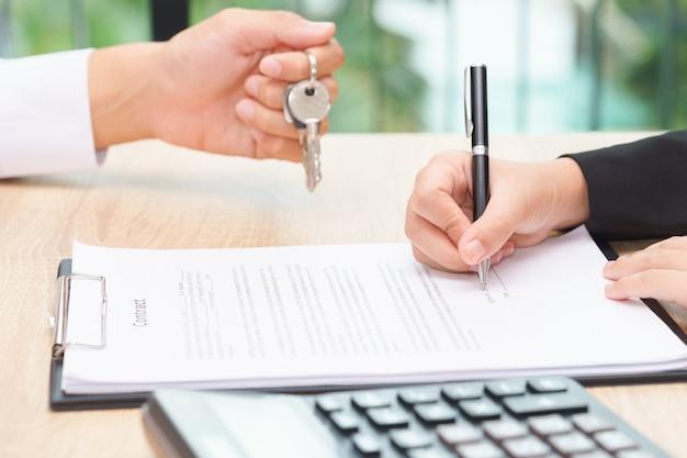 木製の机の上に顧客との契約書の契約書類の上にキーを与えるビジネスマン