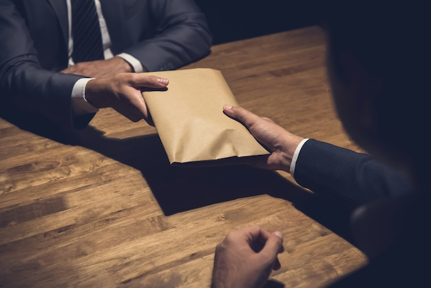 Businessman giving money in the envelope to his partner in the dark