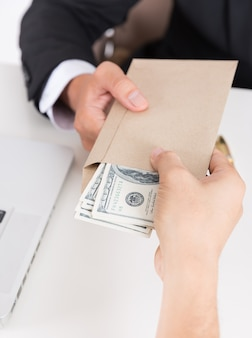 Businessman giving money in the envelope while making deal financial corporate.