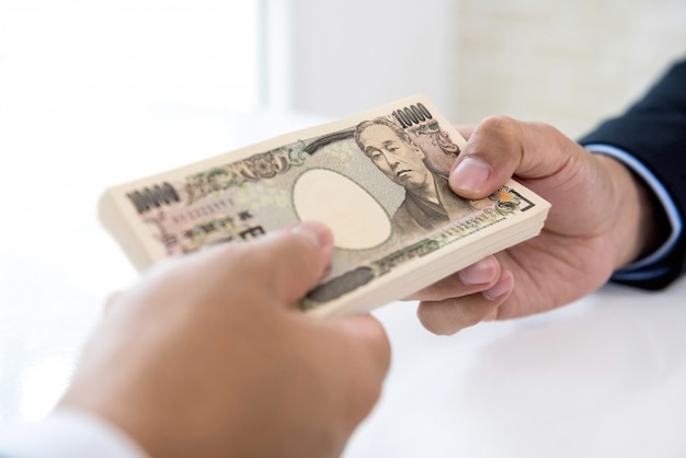 Businessman giving money in the form of japanese yen to his partner