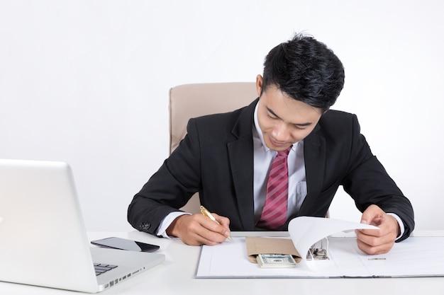 作成中に封筒にお金を与えているビジネスマンは、文書ファイルに署名しました。