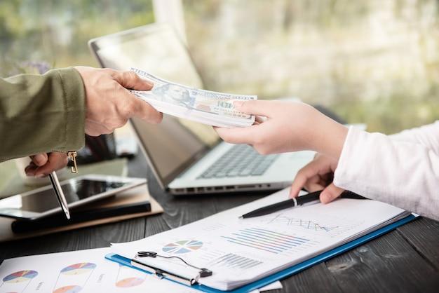 Бизнесмен дает деньги своему партнеру при заключении контракта