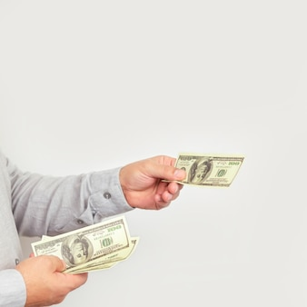 Businessman giving money us dollar bills close-up.