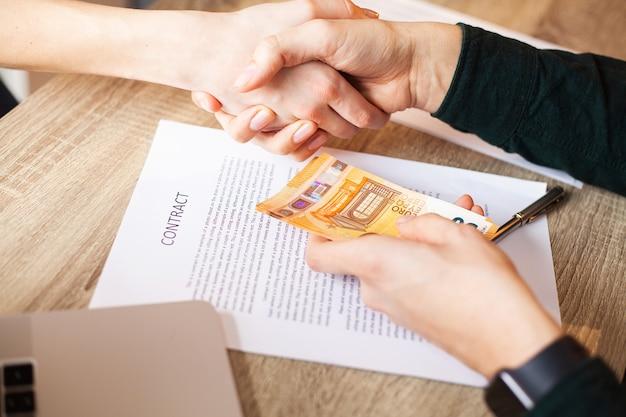 不動産契約と金融企業の契約に合意しながらお金を与える実業家