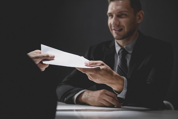 Businessman giving money in white envelope to partner