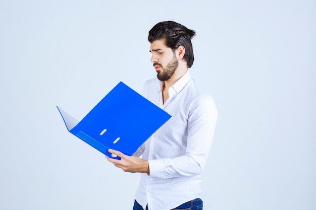 Un uomo d'affari che fa pose con una cartella di segnalazione blu
