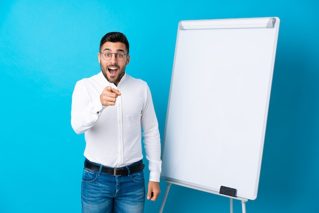 Businessman giving a presentation on white board giving a presentation on white board and surprised while pointing front